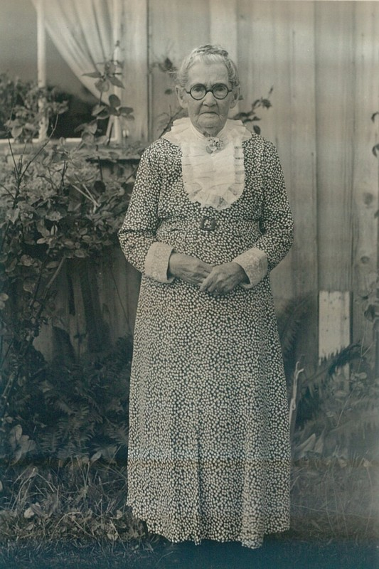 Portrait of old woman in patterned dress.